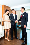 Manager greeting guests in Asian hotel Stock Photos