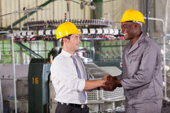 Manager handshaking worker. Factory manager handshaking with african american worker Royalty Free Stock Image