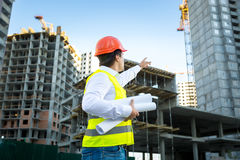 Manager in hardhat pointing at crane on building site Stock Photo