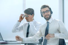 Manager with the headset works in a modern office stock photography