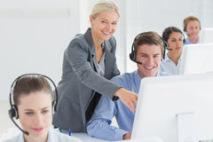 Manager helping call centre employee Stock Image