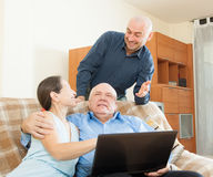 Manager helping to senior couple with laptop Stock Image