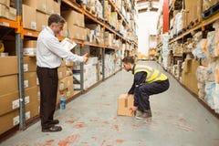 Manager het letten op arbeiders dragende dozen stock afbeelding