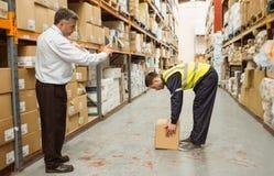 Manager het letten op arbeiders dragende dozen stock fotografie