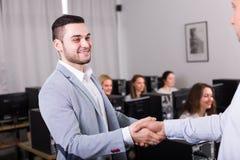 Manager het schudden hand van werknemer stock foto