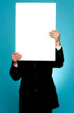 Manager hiding his face behind white banner ad Royalty Free Stock Images