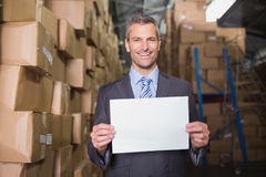 Manager holding blank board in warehouse. Portrait of smiling male manager holding blank board in warehouse Stock Images