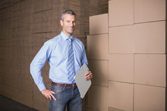 Manager holding clipboard against boxes in warehouse Royalty Free Stock Photography