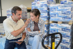 Manager holding clipboard and worker in warehouse Royalty Free Stock Image