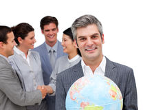 Manager holding a globe in front of his team Royalty Free Stock Images