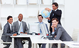 Manager holding a globe with his team Royalty Free Stock Photography