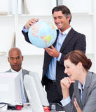 Manager holding a globe while his team is working Stock Photography
