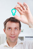 Manager holding lightbulb over head Royalty Free Stock Photo