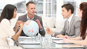 Manager holding a terrestrial globe in a meeting Stock Image