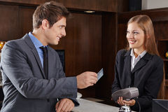 Manager at hotel reception paying with credit card Royalty Free Stock Images