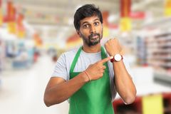 Manager at hypermarket showing wristwatch. Indian manager man at hypermarket or supermarket showing wristwatch with index finger and angry expression as you are royalty free stock images