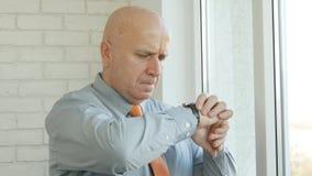 Manager im B?ro-Aufenthalt und Wartezeit, die schaut, um Uhr zu ?bergeben Zeit ?berpr?fend lizenzfreies stockbild