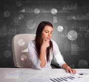 Manager im B?ro, das Berichte und Statistiken mit Tafelhintergrund macht stockfotografie