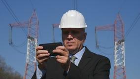Manager im Energiewirtschafts-Text unter Verwendung eines Handys lizenzfreies stockbild