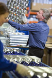 Manager inspecting trays of aluminium light fittings in factory Royalty Free Stock Photos