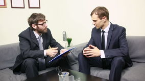 Manager interviewing a male applicant in his office. Two men in business suits. Manager interviewing a male applicant in his office stock video