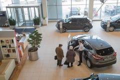 Manager, klant en auto's in toonzaal van het handel drijven Nissan in Nizhny Novgorodcity in 2018 royalty-vrije stock afbeelding