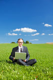 Manager with laptop in a green field Stock Photos