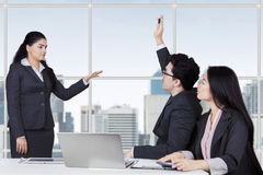 Manager let her employee to ask. Young female business leader in a meeting and let her partner to ask, shot in the office Royalty Free Stock Images