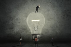 Manager on lightbulb calling his subordinate. Young male manager standing on a bright lightbulb and calling his subordinate with a megaphone Royalty Free Stock Photos
