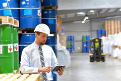 Manager in a logistic company work in a warehouse with chemicals. Checking goods with tablet royalty free stock photography