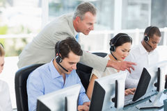 Manager looking at executives with headsets using computers Royalty Free Stock Photos