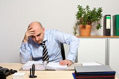 Manager looks demotivated in his files. Stressed out manager looks demotivated in his files royalty free stock photos