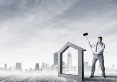 Manager man crashing stone home as symbol for real estate insurance. Determined businessman going to break with hammer house concrete figure royalty free stock photography
