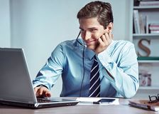 Manager man talking on the phone and looks at laptop. Photo of successful manager working with financial data in the office. Business concept stock image