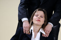 Manager massaging woman sitting on chair Stock Images