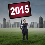 Manager on the meadow with number 2015. Male entrepreneur standing on the field while holding a board with number 2015 Royalty Free Stock Photography
