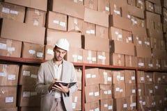 Manager met agenda tegen dozen in pakhuis royalty-vrije stock foto