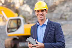 Manager mining site. Happy manager in mining site holding ore Royalty Free Stock Image