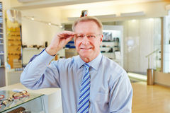 Manager with new glasses at. Elderly manager with new glasses at optician retail store royalty free stock photos