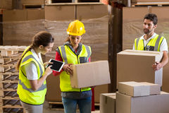 Manager noting on digital tablet while workers carrying cardboard boxes Royalty Free Stock Photography