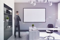 White and gray company manager office, poster ton. Manager office interior with a large window, a table with a chair and a computer on it. A gray bookcase. A royalty free stock images