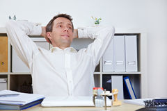Manager in office relaxing. Happy business manager in office relaxing and leaning back Stock Image