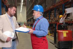 Manager and older worker in warehouse. Manager and older worker browsing papers in warehouse, other worker in uniform with box in background stock images