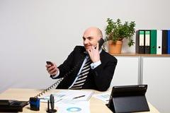 Manager op de telefoon terwijl hij zijn smartphone controleert stock fotografie