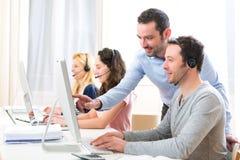 Manager opleiding jonge aantrekkelijke mensen op computer stock afbeelding