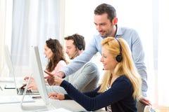 Manager opleiding jonge aantrekkelijke mensen op computer stock afbeeldingen