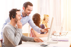 Manager opleiding jonge aantrekkelijke mensen op computer stock foto