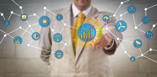 Manager Optimizing Energy Consumption Via IoT. Unrecognizable corporate manager optimizing energy consumption via the Internet of Things. Information technology Stock Photo