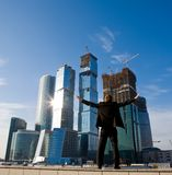 Manager with outstretched arms against skyscraper. Businessman standing with outstretched arms against skyscraper in Moscow City Stock Photos