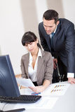 Manager overseeing business woman Stock Image